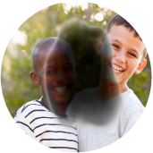 Two young boys are standing together and smiling. A dark, blurry spot in the center of the image blocks part of their faces and bodies.