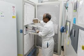 image tagged with holds, containers, lab coat, adult, science, …;